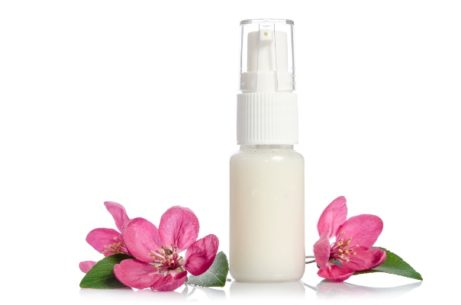 Face cream bottle with pink flower isolated on white